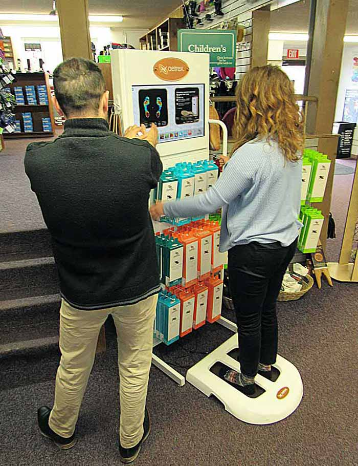 A Family Footwear Center Employee helps Customers use a Foot Scanner